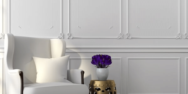 image of architectural molding, bedroom or sitting room with off white walls, wall paneling and a sitting chair white with end table