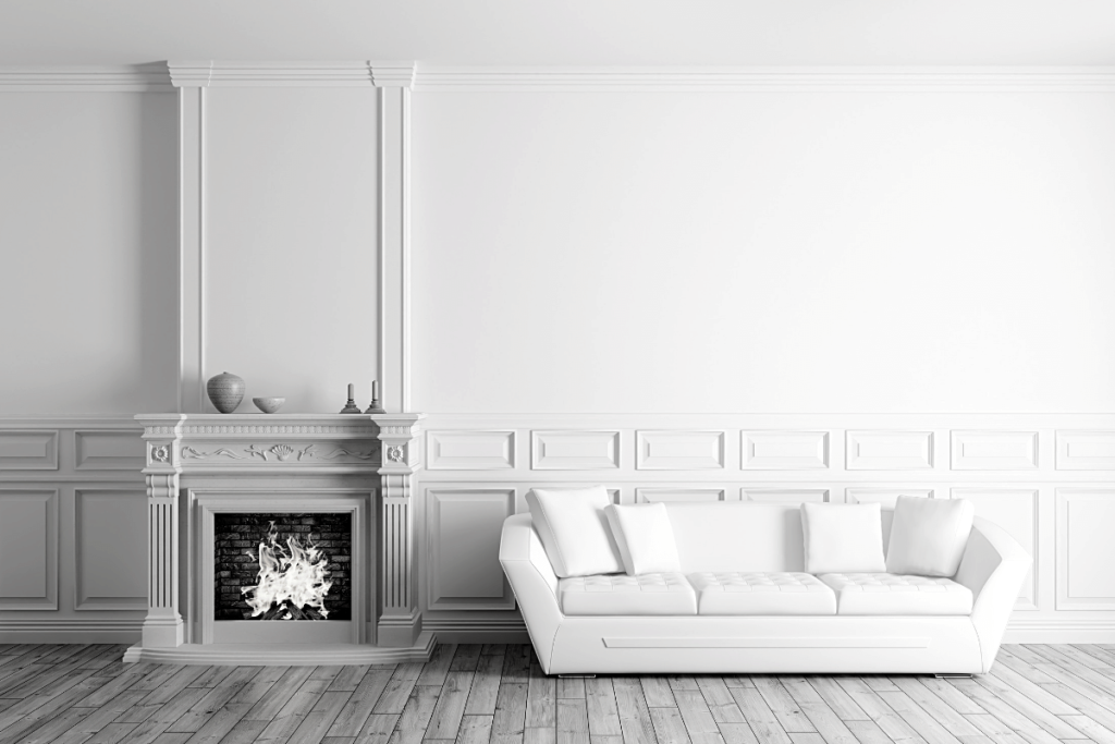black and white image of white leather couch next to a simple fireplace with wood trim accent, wall behind couch has white wainscoting on the lower third